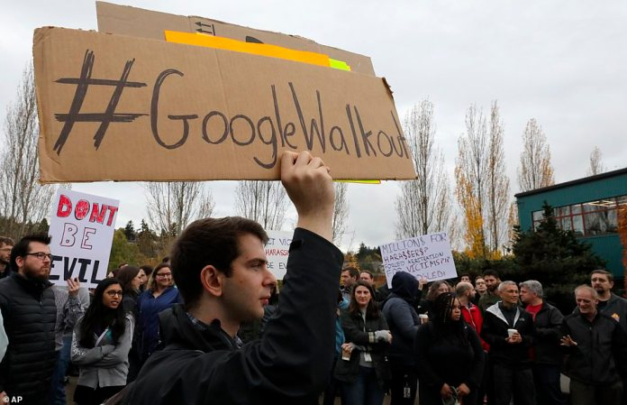 "A Seattle-based Google employee holds a sign posted ""#GoogleWalkout"" during a protest on Thursday in Seattle"