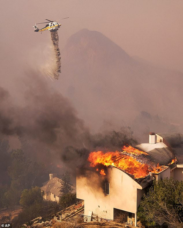 A helicopter drops water over fierce flames charging into Malibu on Friday afternoon