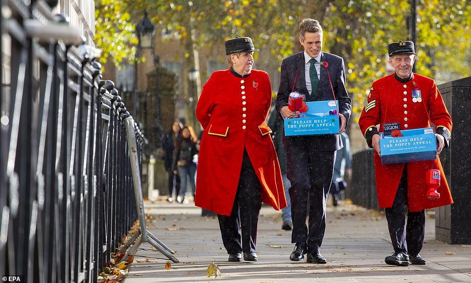 Le secrétaire d'État britannique Gavin Williamson se joint à Anthony Hunt (à gauche) et à June Lowe (à droite), retraités de Chelsea, pour recueillir des dons en faveur de la Royal British Legion à Londres.