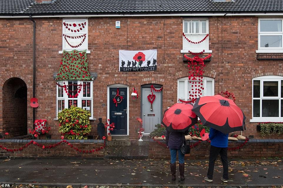 Les gens regardent une maison de Station Road, Aldridge à Walsall, devenue Poppy Road. Près de 100 maisons ont été décorées de 24 000 coquelicots rouges et de statues de soldats représentant les habitants qui ont enduré et perdu la vie durant la Première Guerre mondiale.
