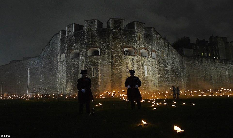 Les Yeomen Warders se tiennent parmi des milliers de flambeaux à la tour de Londres pour commémorer le centenaire du jour de l'armistice à Londres