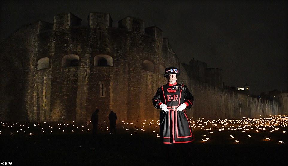 Un Yeomen Warder se tient parmi des milliers de torches à la tour de Londres pour commémorer le centenaire du jour de l'armistice.