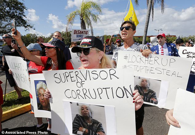 Am Freitag, dem 9. November 2018, in Lauderhill, Florida, protestiert eine Menschenmenge vor dem Büro des Broward Supervisor of Elections. In einem strengen Gouverneur von Florida, im Senat und in der Landwirtschaftskommission ragt ein mögliches Nachzählen. (AP Foto / Joe Skipper)