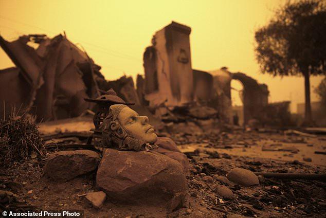 Ein Kunstwerk befindet sich vor den verbrannten Überresten von zu Hause Freitag, 9. November 2018, das durch ein Lauffeuer zerstört wurde, das Donnerstag durch die Gegend im Paradise, Kalifornien (Kalifornien, USA) fiel. (AP Photo / Rich Pedroncelli)