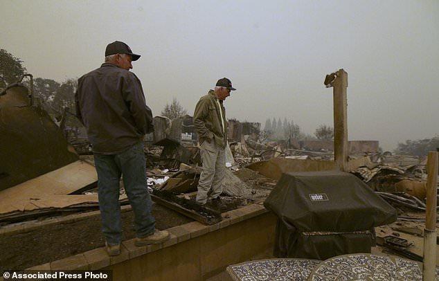 Larry Marple, rechts, in Begleitung seines Sohnes Rod Marple, schaut am Freitag, den 9. November 2018, auf die verbrannten Überreste seines Hauses, das durch ein Lauffeuer, das am Donnerstag durch die Gegend ging, in Paradise, Kalifornien, zerstört wurde. AP Photo / Rich Pedroncelli)