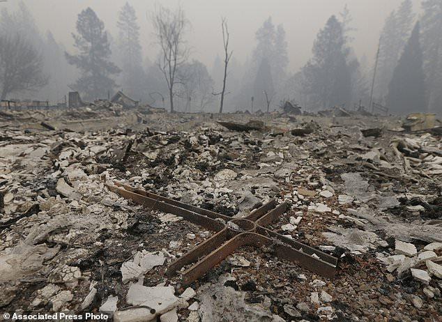 Une croix est parmi les décombres de l'église Notre-Sauveur luthérienne, le vendredi 9 novembre 2018 à Paradise, en Californie. L'église a été détruite par un feu de forêt qui a balayé la région jeudi. Les autorités ont confirmé qu'au moins six personnes sont mortes dans l'incendie qui a détruit plus de 200 000 hectares et détruit au moins 2 000 structures. (AP Photo / Rich Pedroncelli)