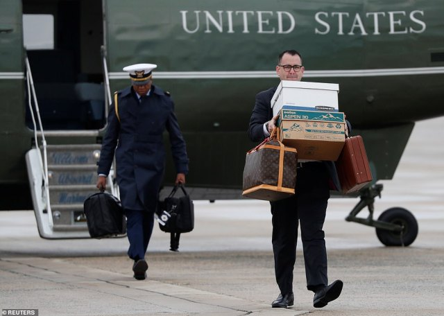A White House staff member carries personal luggage and papers for Trump and Melania as a U.S. military aide carries briefcases containing the military launch codes known as the nuclear football to Air Force One