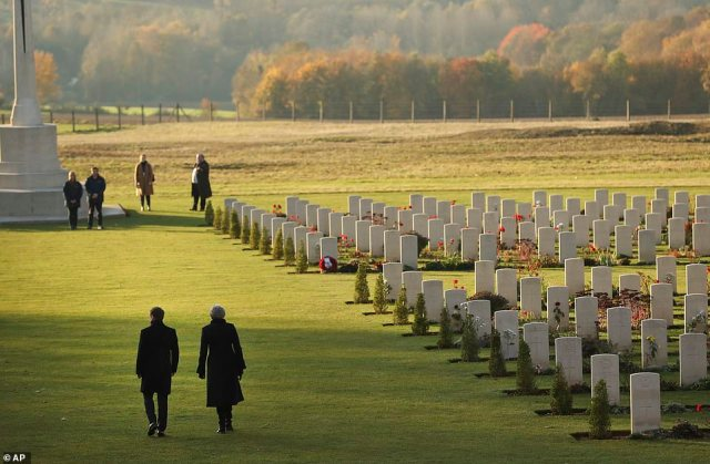 French President Emmanuel Macron (left) and Theresa May walk through the WWI graves at the Thiepval Memorial in France