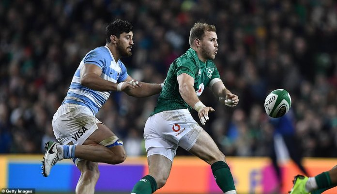 The Irish national Robbie Henshaw passes the ball against Argentina while his side seems to cause problems to his opponents