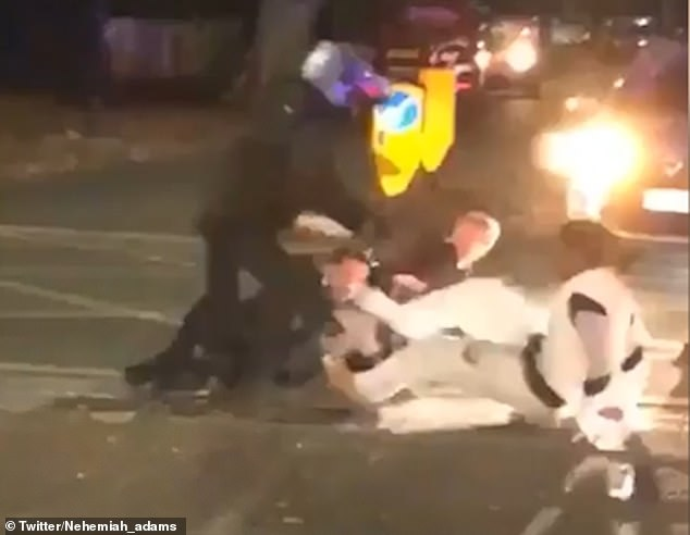 A heroic moped rider (pictured in helmet) eventually manages to get one of the attackers off the officer