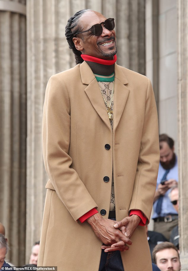 Nuthin' but a G Thang: Donning a long tan coat with a beige turtleneck underneath, the Gin and Juice rapper couldn't keep the smile from his face