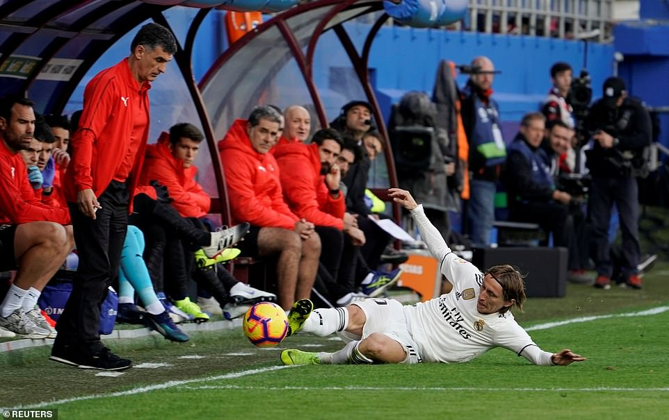 Real Madrid midfielder Luka Modric slides to try and keep the ball in play on the left-hand side