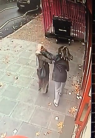 The victim, who is seen wearing a pink headscarf and carrying a black shoulder bag, is almost thrown off her feet as she desperately tries to defend herself