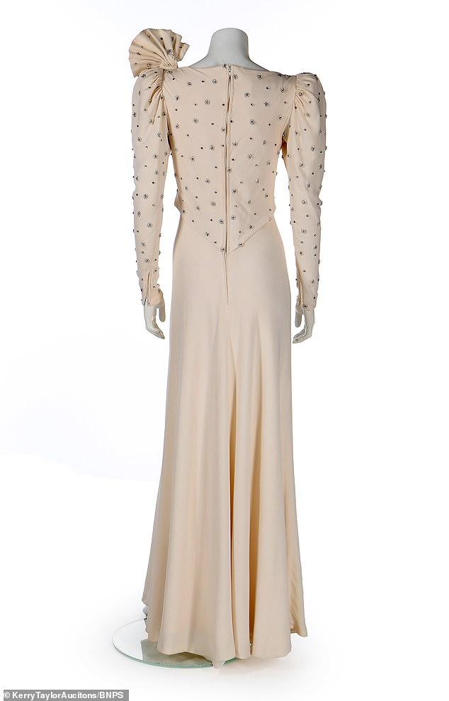 Hay un gran lazo detrás del hombro izquierdo y brillantes joyas incrustadas a lo largo de las mangas y la mitad superior del vestido.