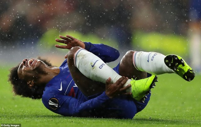 Brazilian forward Willian rolls around in pain after taking a sore one on his ankle during the second half at Stamford Bridge