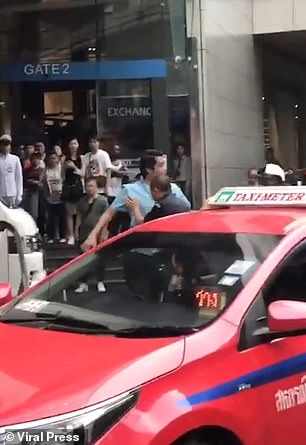 A crowd of onlookers watch from steps to the shopping mall as the man in blue starts to retaliate, throwing punches at the brawling guards