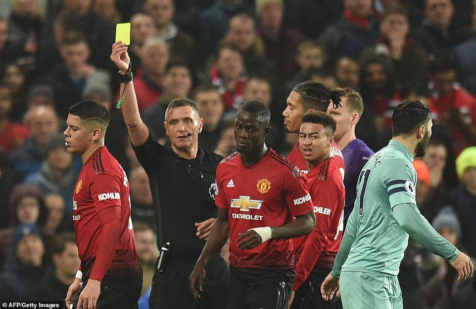 Rojo (left) walks away after being shown a yellow card by referee Andre Marriner for his dangerous challenge