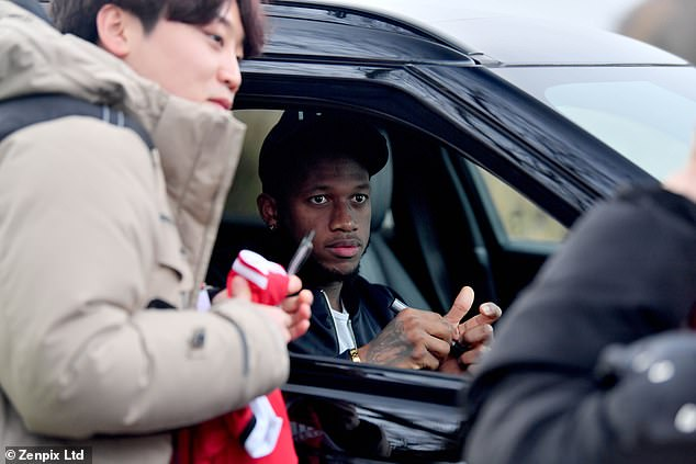Fred signs autographs in front of Carrington as he leaves the club's training base on Friday
