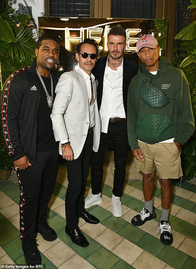 Pals:The father-of-four appeared in high spirits as he joined a host of famous faces, including Pharrell Williams (pictured far right)