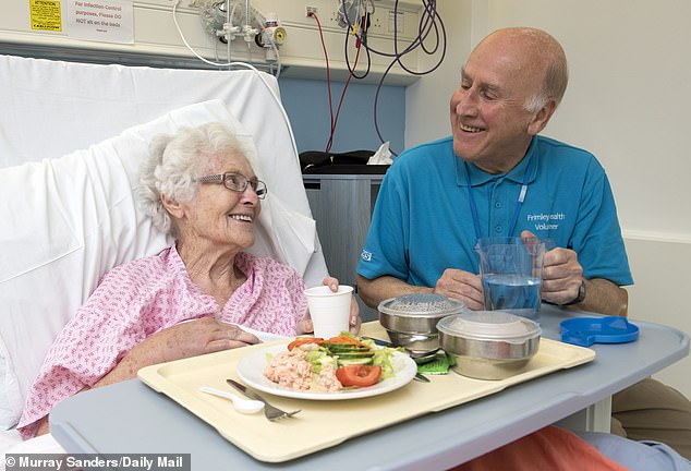 Volunteer Roger Groocock helps patient Mary Charlton with her lunch after she was admitted with a wrsit injury in Frimley Park Hospital in Surrey