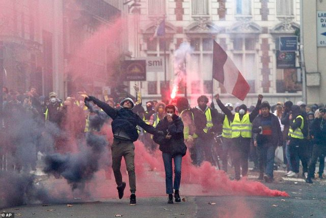 Paris is on lockdown as armed police battle to contain 'yellow vest' demonstrators with more than 700 arrests so far today in the fourth straight weekend of demonstrations over living costs and proposed tax rises in France. Angry protesters have been pictured throwing flares and smoke bombs at police who have returned in kind with tear gas and water cannons