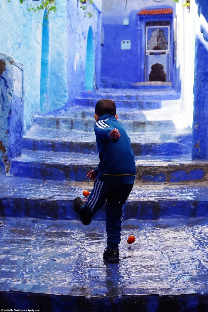 Isabella Smith, from the US, was named young Travel Photographer of the Year. This shot of hers shows a boy playing in the street in Chefchaouen, Morocco. Isabella said: 'This really grabbed my attention! I thought this local boy using oranges as balls was the opposite of kids in my country playing with expensive toys'