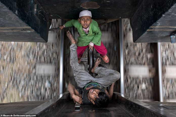 Young boys Taj and Akash, who travel every day from station to station with their mother, beg to make a living in Gazipur, Bangladesh. The image was captured by commended Italian photographer Mauro de Bettio