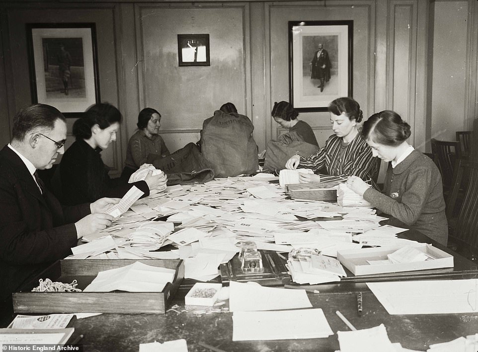 One image captured from the time shows 20 employees engrossed in opening envelopes containing money for the British voluntary hospitals in response to the appeal (pictured in 1939)