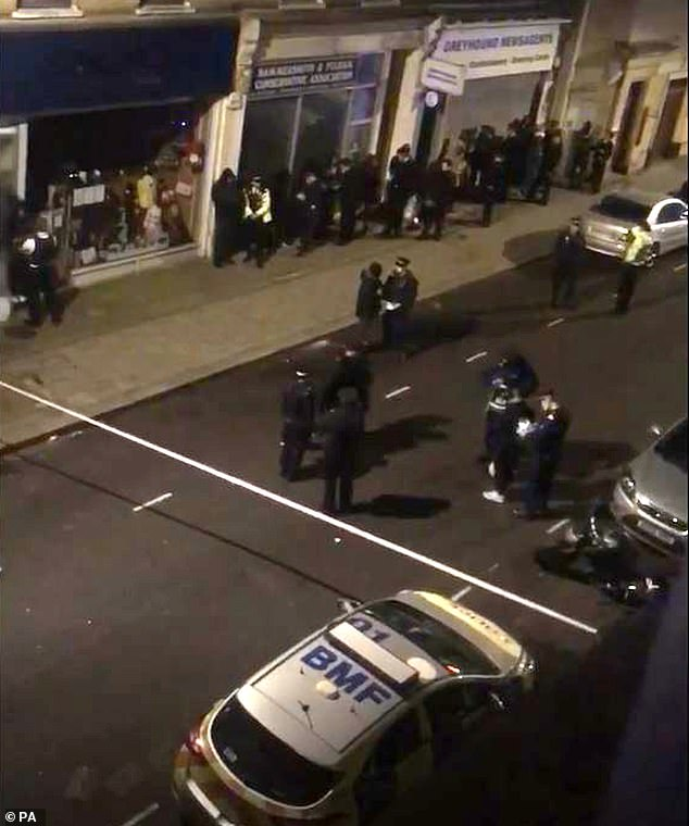 Police officers on the scene shortly after 39 people were arrested at a house party following a stabbing nearby