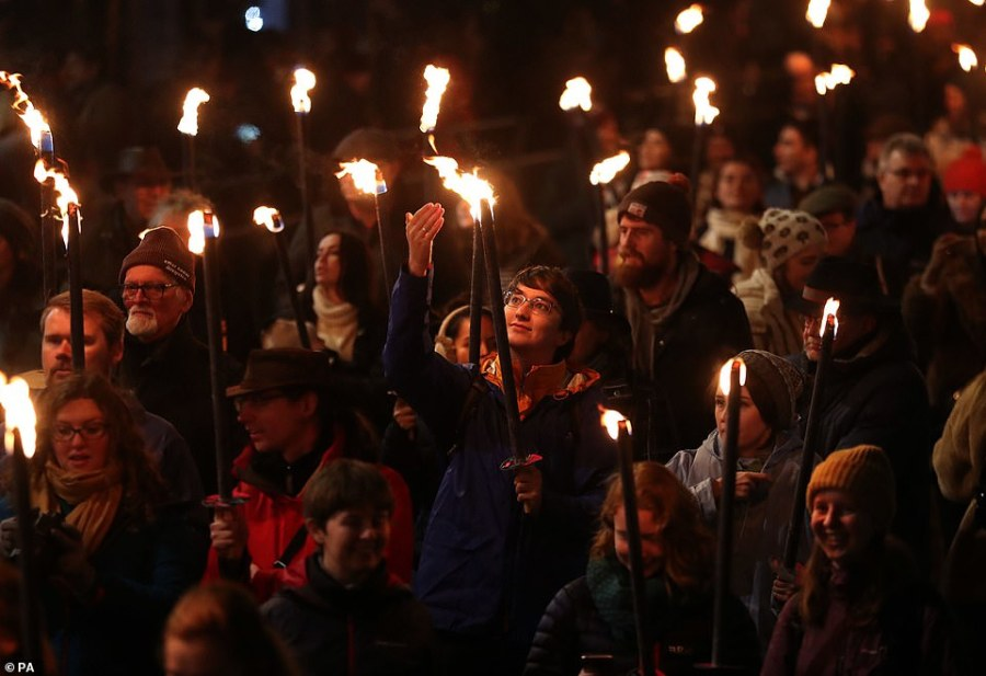 People smile as they take part in a torchlight procession  during Edinburgh's Hogmanay celebrations yesterday
