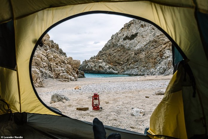 Sometimes the family sleeps outside in tents. In the picture is a sandy beach surrounded by rocks on the Greek island of Crete