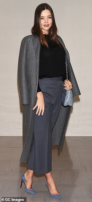 Supermodel strut: The Australian cover girl threw a charcoal grey wool coat over her shoulders, while teetering on blue suede stiletto heels