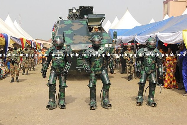 Walking into war: Three men walk in their heavy exoskeletons with an armoured vehicle following behind them during what appeared to be a product launch in Ghana