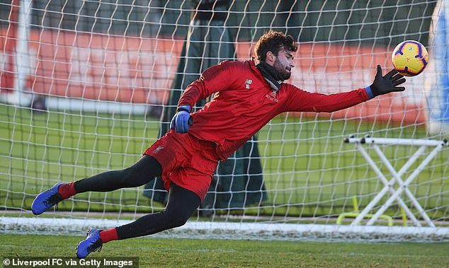 Alisson dives across to make a one-handed save as he prepares to return in goal at Brighton