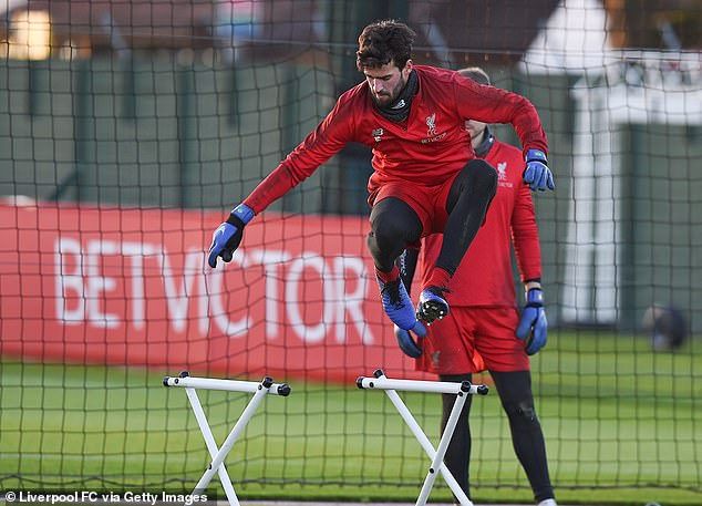 Brazilian goalkeeper Alisson jumps in the air as he was challenged physically by coaches