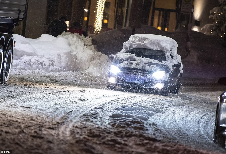 A snow-covered car drives along a snow-covered street in the town of Berchtesgaden, Bavaria, last night
