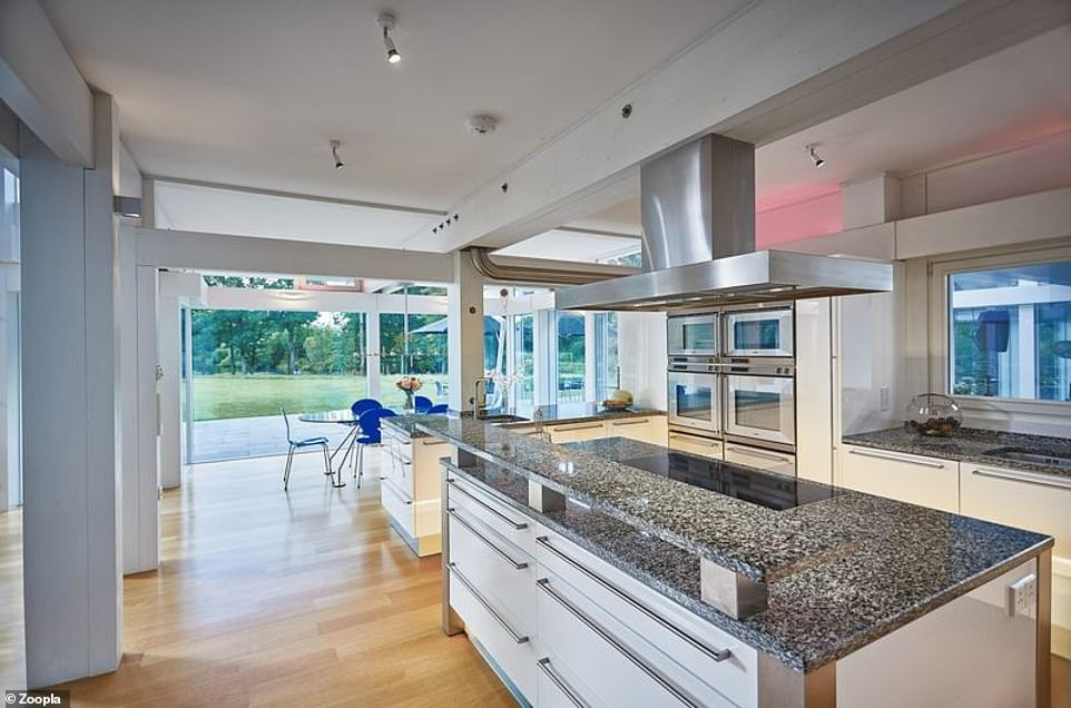 The open-plan living area includes a kitchen with a large island and several ovens