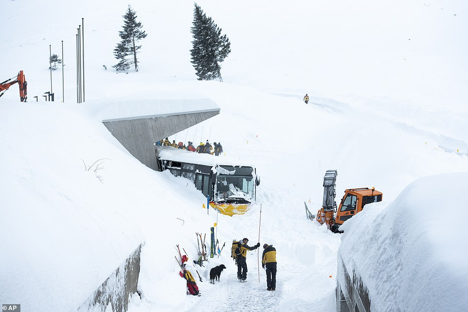 Emergency workers attempt to free a bus trapped in the snow at theHotel Saentis in Schwaegalp