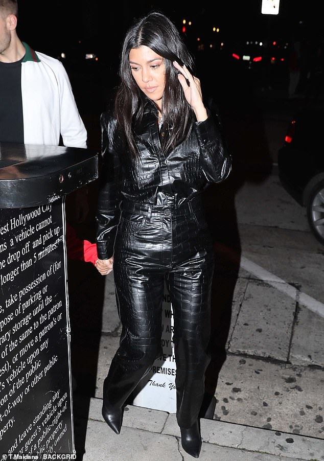 A beautiful appearance: Kourtney wore a complete black suit with pointy black shows, while wearing a silver cross around his neck.