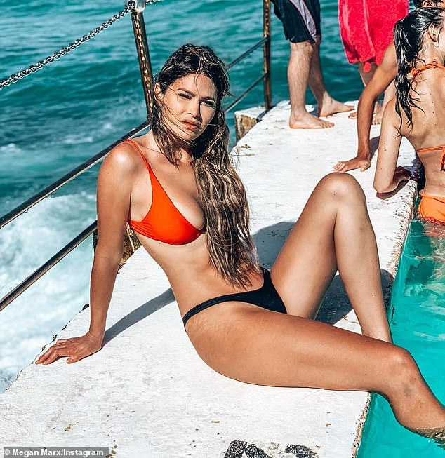 'Stretch marks are hot!' Megan Marx shows off the 'shiny' lines on her thighs as she poses in a skimpy mismatched orange and black bikini