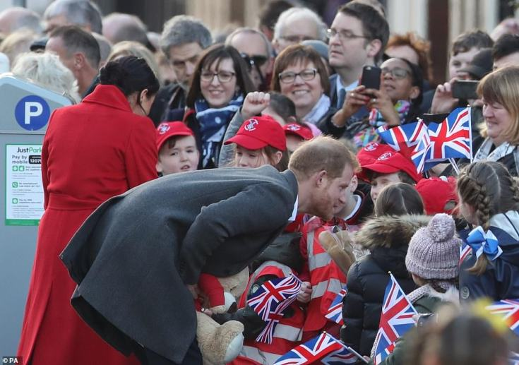 The couple chat to young fans, many of whom were waving flags.Fans handed Meghan bouquets of flowers, while she looked particularly delighted with the gift of handmade paper flowers from a young fan from the nearby Fun Train Day Nursery