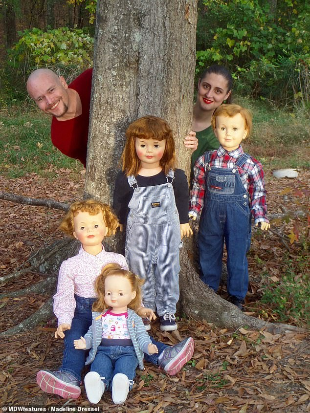 Madeline and Malachi joking around during an outdoor photoshoot with their dolls. They couple insist that they don't see them as surrogate children, but just enjoy their hobby