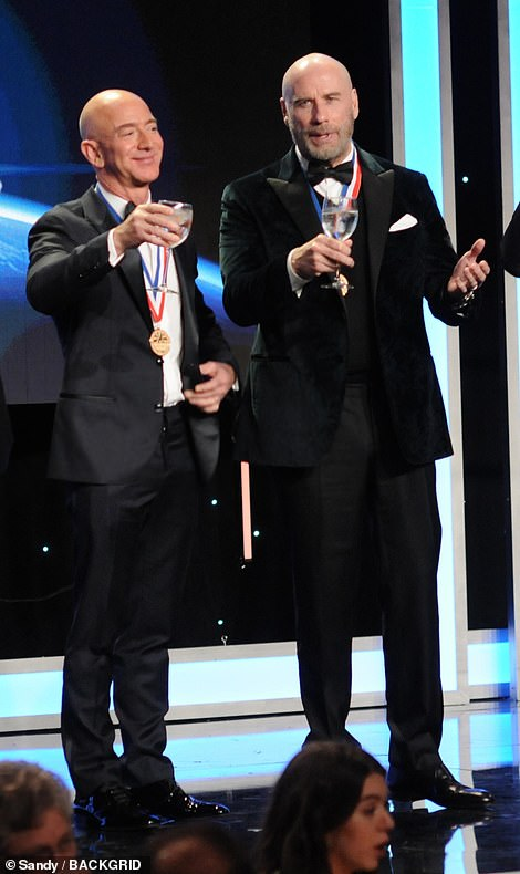 Bezos raises a glass while Travolta addresses the audience