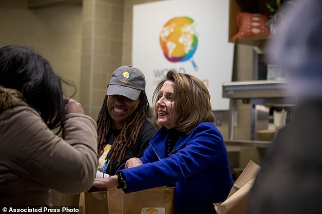 House Speaker Nancy Pelosi of Calif., center, smiles as she helps give out food at World Central Kitchen, the not-for-profit organization started by Chef Jose Andres, Tuesday, Jan. 22, 2019, in Washington. The organization devoted to providing meals in the wake of natural disasters, has set up a distribution center just blocks from the U.S. Capitol building to assist those affected by the government shutdown. (AP Photo/Andrew Harnik)