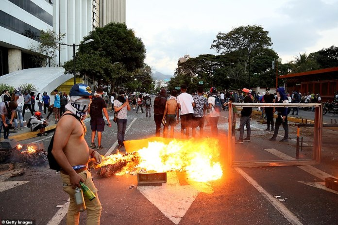 Lighting a fire: A masked demonstrator in Caracas holds bottles as a fire burns in the street during mass protests yesterday, which saw an opposition leader declare himself President and seven people killed in violence across the country
