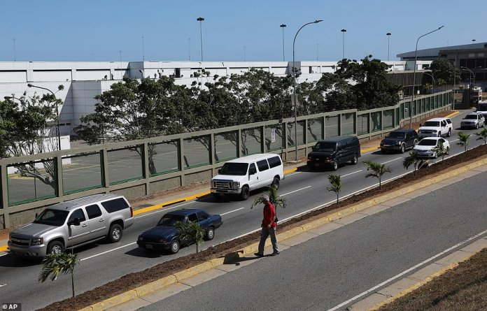 A caravan of large vehicles leave Simon Bolivar international airport after dropping off U.S. embassy employees and their families in La Guaira, Venezuela, today