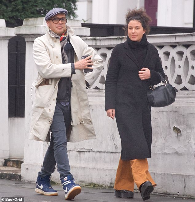 Chilled out: He clad his legs in blue chinos and completed the look with blue Nike trainers as he was joined by a female companion for the outing
