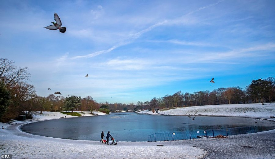People walk past the frozen Sefton Park Lake in Liverpool today as freezing temperatures led to further weather warnings