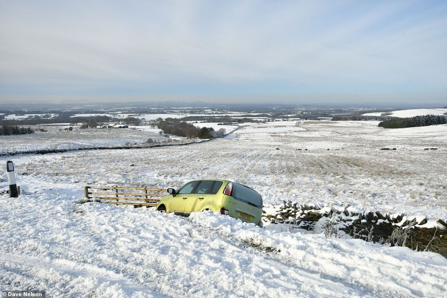 A car abandoned on the side of the road in the snowy and icy conditions today at Rivington Pike, on Winter Hill in Lancashire