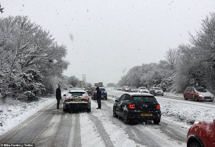 Heavy snow falls on the Redruth bypass in Cornwall this afternoon as drivers stand outside their cars in the extreme weather